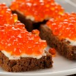 Red caviar on rye bread and butter on white plate — Stock Photo #61459495