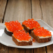 Red caviar on rye bread and butter on white plate — Stock Photo #61459497