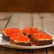 Red caviar on rye bread and butter on white plate — Stock Photo #61459503