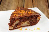 Chocolate apple cake with orange peels on white plate — Stock Photo