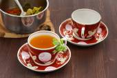 Sea-buckthorn tea with mint in red cups — Stock Photo
