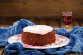 Homemade cake with pink icing and wine on blue background — Stock Photo