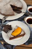 Chocolate cake with mango and black tea on blue cloth — Stock Photo