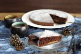 Chocolate cake with pine cones and black tea on blue cloth — Stockfoto
