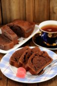 Homemade chocolate cake cut with pink candies and tea in blue cu — Stock Photo