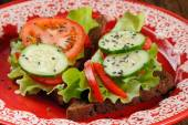 Rye sandwich with salad leaves, tomato, cucumber, bell pepper in — Stock Photo