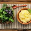 Polenta with basil shoot in wooden bowl with green salad and woo — Stock Photo #76965111