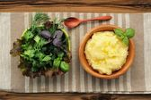 Polenta with basil shoot in wooden bowl with green salad and woo — Stock Photo