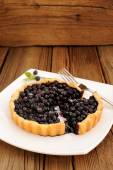 Homemade blueberry tart cut in square white plate with fork and — Stock Photo