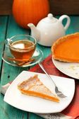 Pumpkin pie, tea in glass cup, white teapot and fresh pumpkin on — Stock Photo