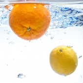 Lemon and orange in the water — Stockfoto