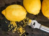 Peeling lemon rind to add zest — Stock Photo