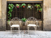 Two white metal chairs in the old town of Barcelona — Stock Photo