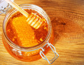 Jar of honey with honeycomb and dipper on wooden background — Stock Photo