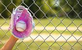 Ręka gracza baseballu różowy rękawiczka i piłki na pole — Zdjęcie stockowe