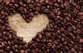 Hecha de granos de café en la superficie de madera en forma de corazón — Foto de Stock