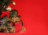 Christmas. Gift Box under Christmas Tree over Red Background — Zdjęcie stockowe
