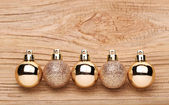 Gold Christmas Balls Over Wooden Background.  — Photo