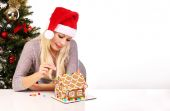 Girl making gingerbread house. Young woman with Santa Hat — Stok fotoğraf