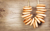 Bagels on rope over wooden background — Stock Photo