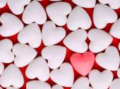 Pink heart between a pile of white hearts. Candy Hearts backgrou — Stock Photo