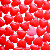 Hearts background. Pink heart between a pile of red hearts — Stock Photo