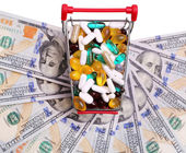 Shopping cart full with pills and capsules over dollar bills — Stock Photo