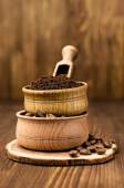 Ground coffee and beans in a wooden bowl — Stock Photo