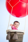 Baby girl on hot air balloon in the sky — Stock Photo
