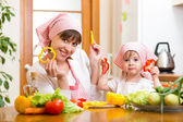 Kid girl and her mother cooking in kitchen at home — Stock Photo