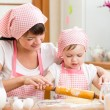Mother and kid prepare cookies using a rolling pin — Stockfoto