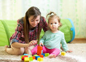Mom and child daughter play block toys home — Stock Photo