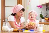 Kid girl with her mom making dough in the kitchen — Stock Photo