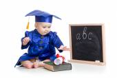 Baby in academician clothes  with book at  blackboard — Stock Photo