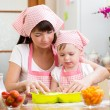 Young woman and her daughter making berry fruit cake — Stockfoto