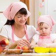 Mother and daughter making apple pie together — Stock Photo #53794645