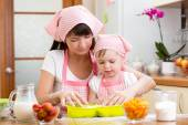 Young woman and her daughter making berry fruit cake — Stock Photo