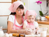 Mother and daughter making cookie dough together at kitchen — Stock Photo