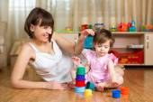 Kid girl and mother play together with cup toys — Stock Photo