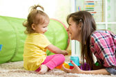 Child girl and her mother playing together with toys — Stock Photo