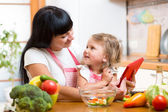 Mother and child preparing vegetables together at kitchen and lo — Stock Photo