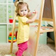 Child girl draws on white board — Stock Photo #54259237