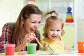 Cute mother teach her daughter kid to paint — Foto de Stock