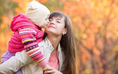 Beautiful woman with kid girl outdoors in fall. Child kissing mo — Stock Photo