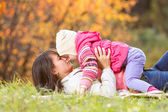 Beautiful mother with kid girl outdoors in fall — Stock Photo