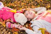 Beautiful mother and kid laying on autumnal leaves outdoors — Stock Photo