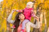 Playful mother with child girl walking outdoors in autumnal park — Stock Photo