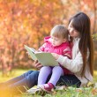 Mother reading a book to kid outdoors in autumn — Stock Photo #54587895