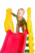 Toddler boy playing on the slide — Stock fotografie