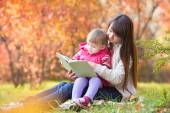 Mother reading a book to kid outdoors in autumn — Stock Photo